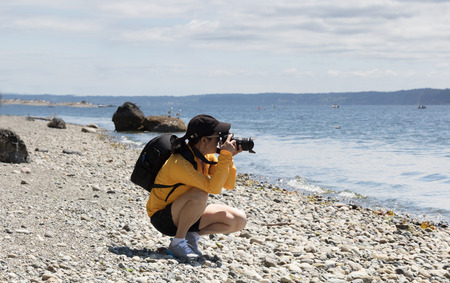 Woman photographer taking photos around the lake during bright summer day photo