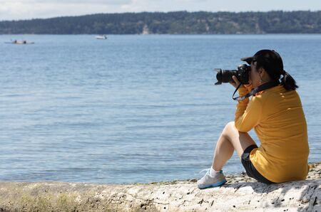 Woman photographer taking photos of lake with boats during bright summer day photo