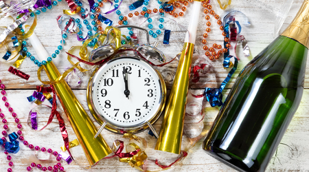Klok met middernacht voor Nieuwjaarsviering omringd door feestvoorwerpen en champagne