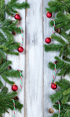 christmas tree branches candy canes and red ornaments forming vertical borders on rustic white wood