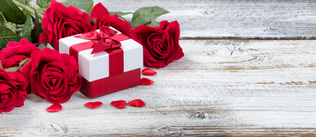 Gift box with red roses and hearts on rustic wood in close up view