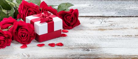 caja de regalo con rosas rojas y corazones en madera rústica en vista de cerca