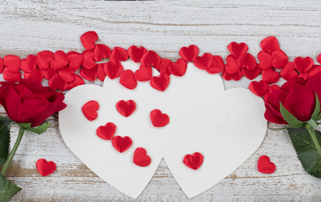 Valentines card with red heart shapes and roses on rustic white wood in flat lay view Stock Photo