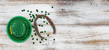 St Patricks day good luck hat and horseshoe with clovers on weathered white wood in overhead view Stock Photo
