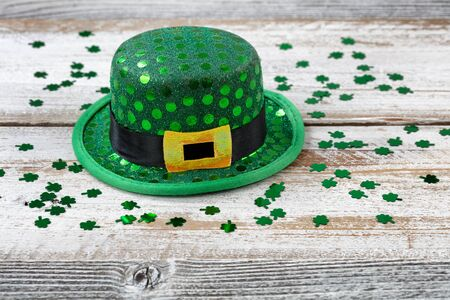 St Patrick day good luck hat with shiny clovers on rustic white wooden boards in close up view