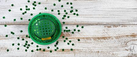 St Patrick day good luck hat with shiny clovers on rustic white wooden boards in overhead view  Stock Photo