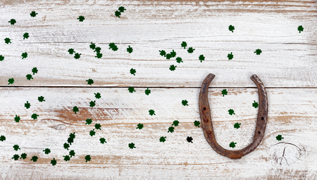 St Patrick day good luck horseshoe with shiny clovers on rustic white wooden boards in overhead view