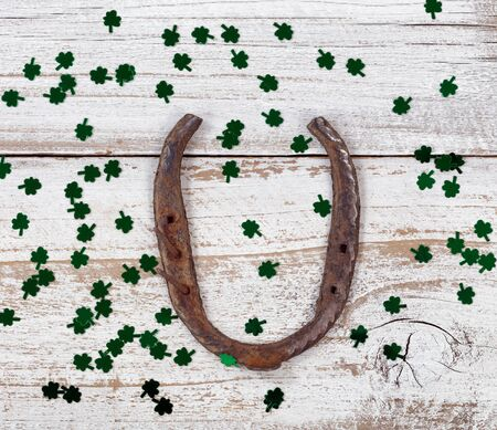 Close up view of a rusty horseshoe for St Patrick day with shiny clovers on weathered white wooden boards