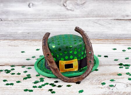 Close up view of a rusty horseshoe resting on hat for St Patrick day with shiny clovers on weathered white wooden boards