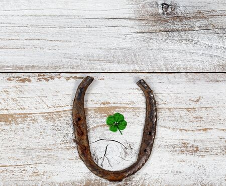 Real four leaf clover in the middle of rusty horseshoe on rustic wooden boards in overhead view