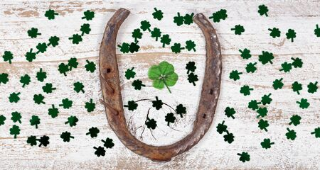 Real four leaf clover in the middle of rusty horseshoe and shiny clovers on rustic wooden boards in overhead view