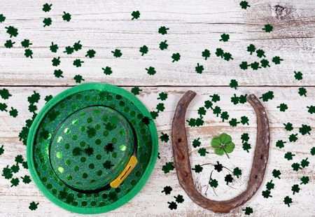 Real four leaf clover in the middle of rusty horseshoe with hat and shiny clovers on rustic wooden boards in overhead view