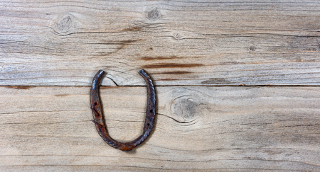 rusty horseshoe on rustic wooden boards in overhead view