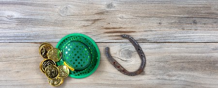 Lucky green hat, horseshoe and gold coins for St Patrick on rustic wooden boards in overhead view