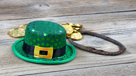 Lucky green hat, horseshoe and gold coins for St Patrick on rustic wooden boards in close up view