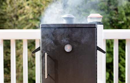 Close up of a cooking smoker with woods in background Stock Photo