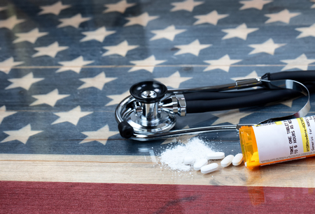 prescription for Hydrocodone or generic opioid with crushed or whole pain killer tablets. Rustic USA flag and medical stethoscope in background for drug addiction concept in America