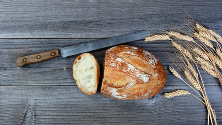 Overhead view of baked whole loaf of bread with cutting knife and wheat stalks on rustic wooden boards Stock Photo