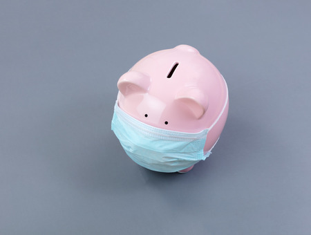 Piggy bank with surgical mask on face Foto de archivo