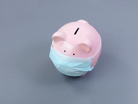 Salvadanaio con mascherina chirurgica sul viso