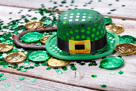 Bright green hat with gold coins, shamrock and rusty horseshoe for Saint Patrick Day on white rustic wooden background in close up format