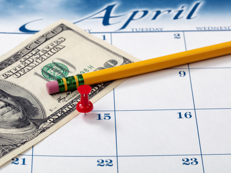 Red pushpin on day of April 15 of calendar for tax income due date reminder with pencil and currency in background