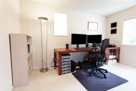 Comfortable computer chair at large work table with computer monitors and other technology equipment in bright home office interior Stockfoto
