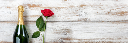 Anniversary background with red rose and champagne on white rustic wood