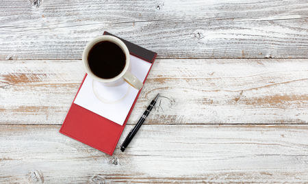 Top view of desktop with red paper notepad, pen and coffee to include stain