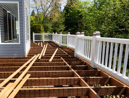 Outdoor wooden cedar deck being remodeled with all floor boards removed