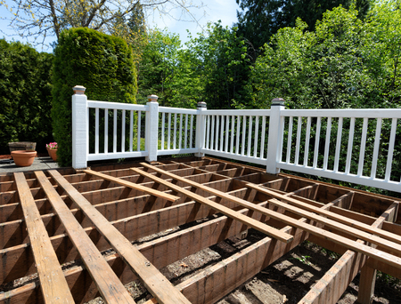 Outdoor wooden cedar deck being remodeled with floor boards being removed