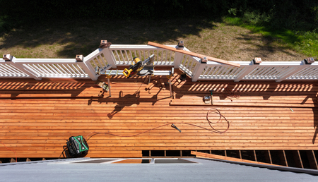 Overhead view of outdoor wooden deck being remodeled with power and hand tools on floor boards