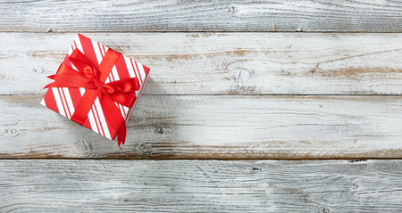 Traditional Christmas giftbox on white rustic wood with plenty of copy space 스톡 콘텐츠