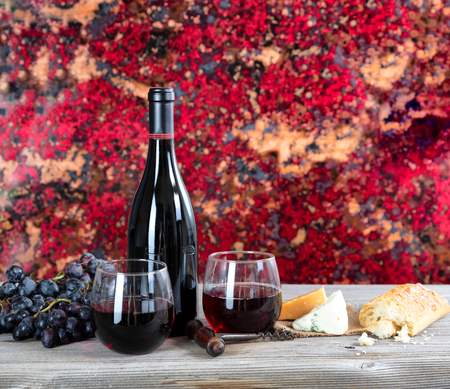 Red wine with cheese and bread on rustic wooden table