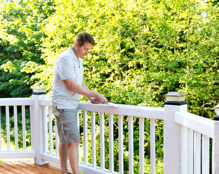 Mature man scraping old paint from outdoor deck railing