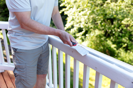 Close up of a mature man scraping old paint from outdoor deck railing