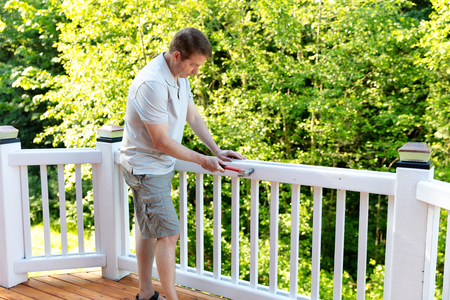 Mature man hammering nails in railing of outdoor deck