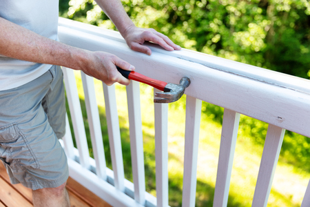 Close up of mature man hammering nails in railing of outdoor deck Stockfoto