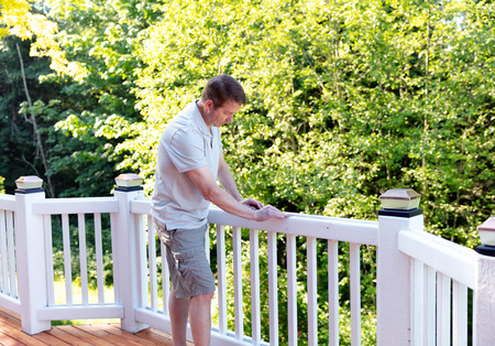 Mature man sanding railing of outdoor cedar deck Stock Photo