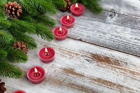 Traditional Christmas holiday candles and evergreen branches with on white rustic wood background