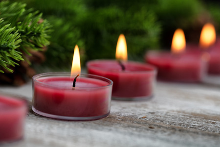 Close up view of traditional glowing Christmas holiday candles with evergreen branches in background