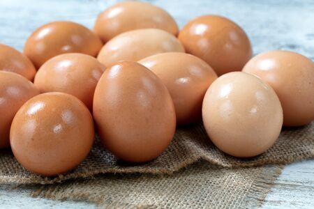 Raw organic brown farm eggs on burlap cloth background