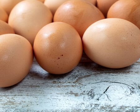 Raw organic brown farm eggs on white rustic wooded background