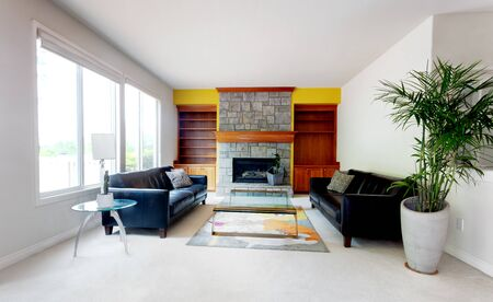 Modern living or family room including large glass table with leather couch and fireplace 스톡 콘텐츠