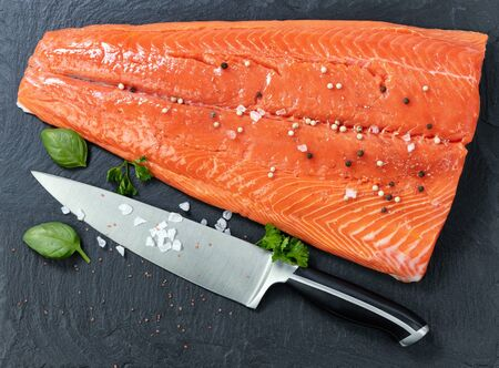 Fresh raw king salmon on natural stone with herbs and seasoning Imagens