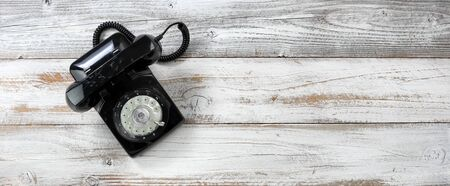 Old fashion rotary dial phone for antique technology concept on white rustic wooden background  스톡 콘텐츠