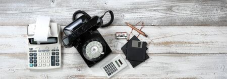 Overhead view of Vintage technologies that includes rotary dial phone and old computer data storage devices plus calculators