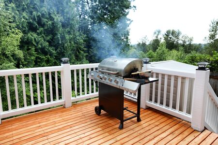 Barbecue grill cooking in open outdoor deck during summer day  스톡 콘텐츠