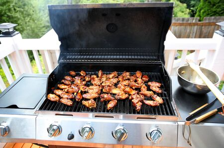 Open barbecue grill cooking chicken wings on outdoor deck during summer day