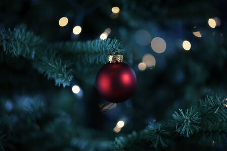 Traditional artificial Christmas tree with red ball ornament and white lights glowing in background 스톡 콘텐츠